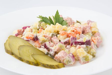 ensaladilla rusa: Olivier Salad with cornichons on a white background