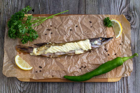coalfish: Baked pike wooden on a table with greens and mayonnaise for decoration Stock Photo