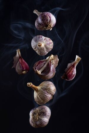 Still life - flying in the smoke garlic on a black background