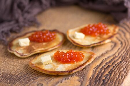 blini: Traditional Russian pancakes with red caviar on a wooden background