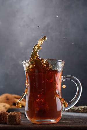a cap of tea with splashes still life on a black background
