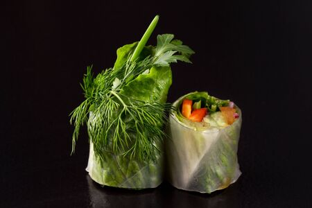 Vegetarian rolls with vegetables on a black background