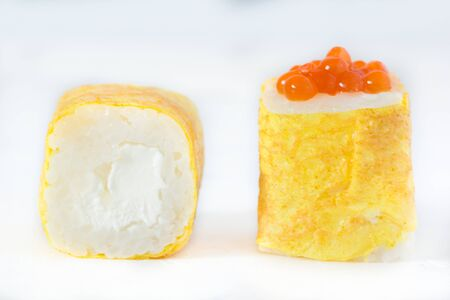 Rolls with caviar in an omelette on a white background, macro
