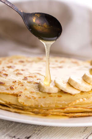 blini: Thin pancakes with butter and honey on a white plate. Maslenitsa. Russian pancakes on a light wooden background. In a rustic style. Country style.
