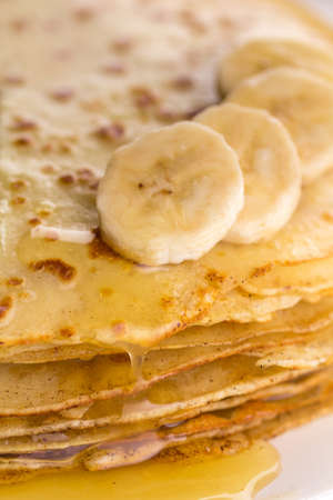 maslenitsa: Thin pancakes with butter and honey on a white plate. Maslenitsa. Russian pancakes on a light wooden background. In a rustic style. Country style.