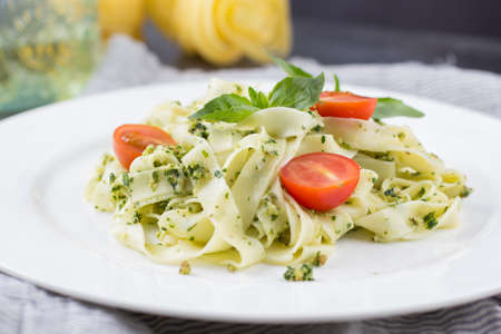 Delicious homemade pasta from basil and arugula with green pesto in a white plate on a dark background. Italian Cuisine Stock Photo