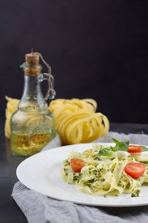 Still life - Homemade pasta from basil and arugula with green pesto in a white plate on a dark background. Italian Cuisine.