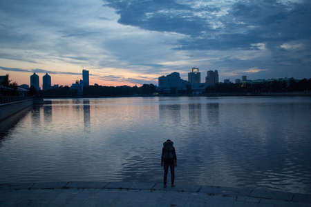 Sunset over the river in the city. Summer in the city. Sunset sky over the river. Man on the background of the setting sun. Traveler in the city looking at the sunset.