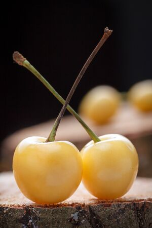 Yellow fresh cherry on a rustic wooden table. Berries on a wooden cut.