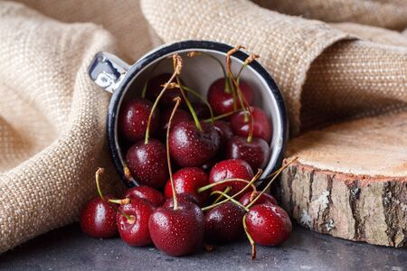 Red cherry in an enameled mug on a background of textile sackcloth. Fresh juicy berries.