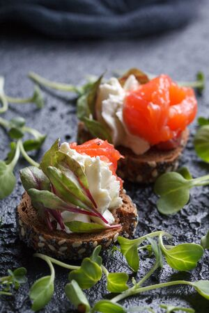 Delicious canape with salmon, cottage cheese, olive with micro greens on a dark background. Cold appetizer on a black background. Stock Photo - 81804414