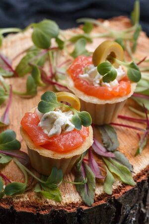 Delicious canape with salmon, cottage cheese, olive with micro greens on a dark background. Cold appetizer on a black background.