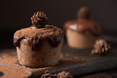 Czekoladowe muffiny, ozdobione małym stożkiem na ciemnym tle drewnianym. Niski klucz. Cupcakes wylewa się z ciemnej czekolady i kakao w proszku. Cupcakes z niezwykłą dekoracją.