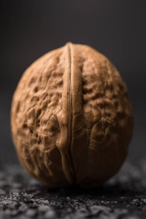 albero nocciolo: A beautiful large walnut in a shell on a black background. Macro. Fresh Harvest. Walnuts on a black surface.
