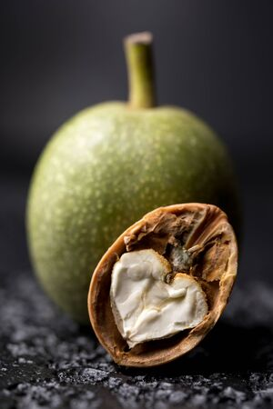 albero nocciolo: A fresh green walnut in the peel is fresh from the tree. Walnut on a black background. Macro. Fresh Harvest. Archivio Fotografico
