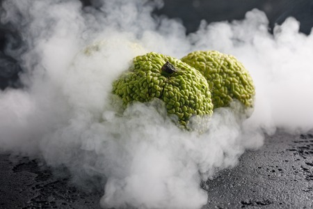 hedgeapple: Adams apples on a black background in smoke. Adams apples, like dragon eggs wrapped in smoke. A strange fruit.