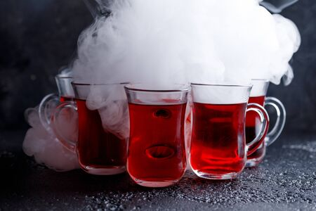 carbondioxide: red cocktail with ice vapor. red cold tea with steam on a black background. red drink in the smoke.