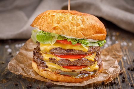 Big hamburger with three beef cutlet and vegetables on wood background.