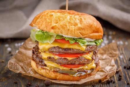 Grande hamburger con una cotoletta di tre manzo e verdure su fondo di legno. Archivio Fotografico - 87171476
