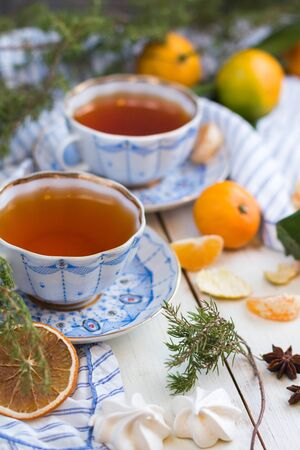 Christmas morning. Tea drinking. A beautiful still-life with tangerines and two cups of hot tea.
