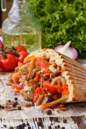 A dish of pita bread stuffed with grilled meat, then chopped meat and fresh vegetables. Stock Photo