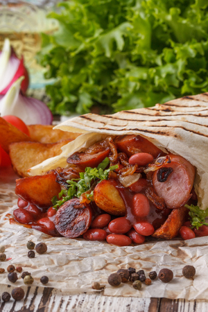 Sturdy and original shaurma with beans and sausages. Stock Photo