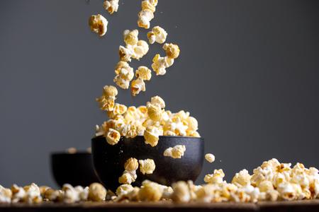 Schwebendes Popcorn um eine Keramikschale. Appetitliches Stillleben.