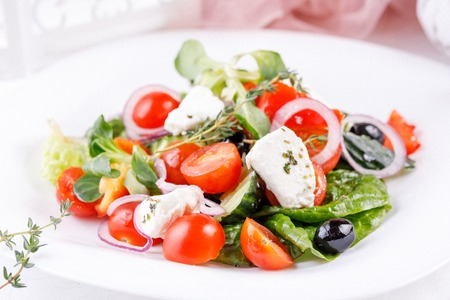 Appetizing and tempting Greek salad with micro greenery. Close-up.