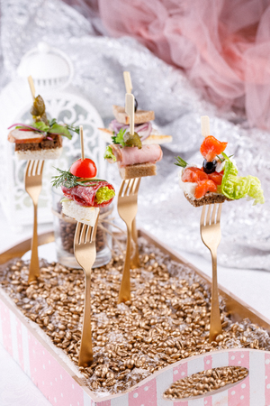 Original canapes on forks. Exquisite still life. Close-up.
