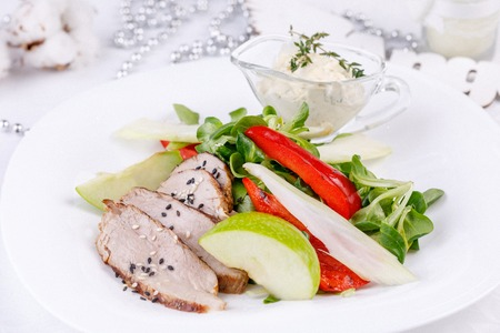 Meat cut with vegetables and creamy garlic sauce. Close-up. Imagens