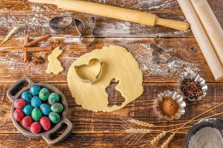 Still life on a wooden background. Pastry for cookies with figured forms for Easter baking.