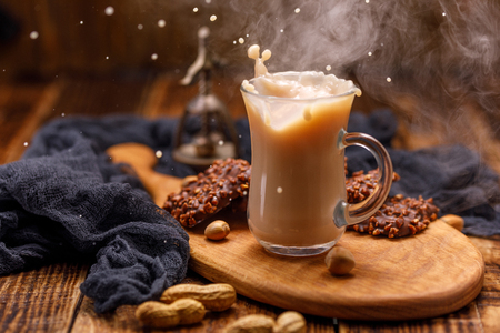 Smoking, tea with milk and chocolate biscuits with nuts for breakfast are spilled from the cup. Tea with biscuits in a glass cup with a splash.