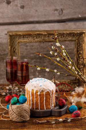 Easter greeting card. A table served for Easter. Fresh Russian cake and dyed quail eggs on a wooden background. With an ancient frame in the background. Stock Photo