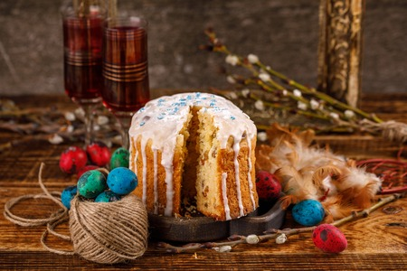 Cahors and Easter treat. Sliced home traditional Easter cake on a wooden table with decorations for the holiday. Spring holiday.