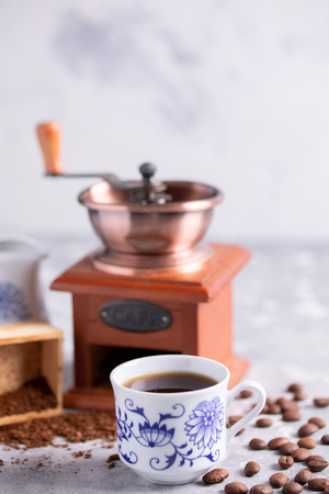 Grains of coffee fall out of a vintage coffee grinder. Hot black coffee in a beautiful porcelain cup on the table. A beautiful coffee composition with a place under your text.