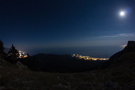 At the top of the Ai-Petri mountain peninsula of Crimea and a magnificent view of the night city. Mountain landscape. Stock Photo