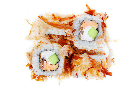 Seductive sushi rolls with avocado eel and cream cheese in tuna flake top view. Isolated on white background.