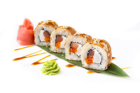 Fresh and original sushi rolls with smoked tuna and Philadelphia cheese in an omelette laid out on a banana leaf. Isolated. Sushi roll on a white background. Sushi Japanese cuisine in the restaurant. Close-up. Japanese restaurant menu.