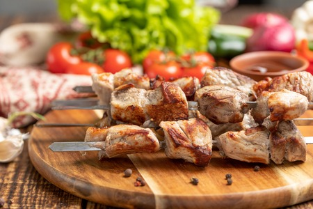 Juicy kebabs from pork on skewers laid out on a decorative board with fresh vegetables. Still-life on a wooden background. 스톡 콘텐츠