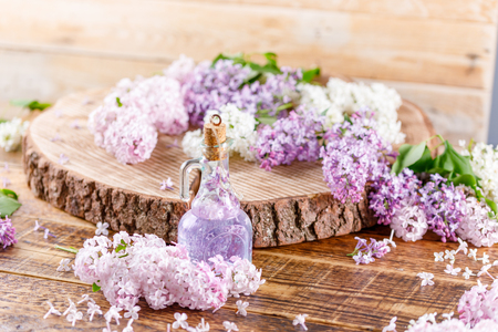 Delicate lilac flowers and lilac tincture in a glass beautiful bottle on a wooden slit. Still-life on a wooden background. Stock Photo