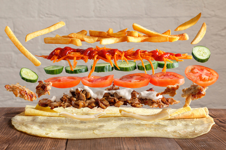 Shaurma. Traditional lavash dish with levitating ingredients from meat and vegetables.