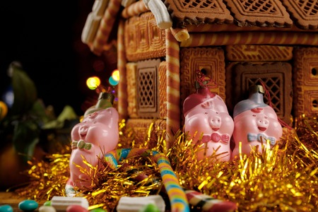 Three little pigs near the gingerbread house and New Year's sweets. Close-up.
