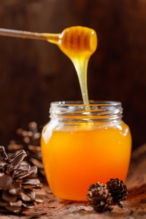 Honey flowing from the chopstick into a glass jar against the background of tree bark and cones. Close-up.