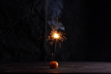 Sparkler in tangerine. Sparkler forming beautiful of star shape. Darkness is all around and effect of sparkling is amazing. 免版税图像