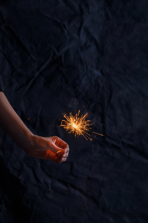Female hand holding a burning sparkler. Christmas sparkler holiday background for xmas new year.