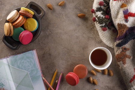 A cup of coffee or tea with macarons and a notebook with colored pencils and a warm sweater. The concept of autumn or winter. Flat lay, top view Foto de archivo - 114204733