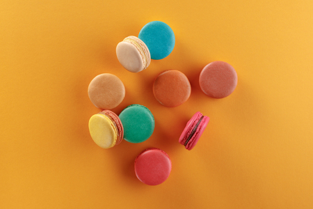 Sweet and colorful french macaroons on a yellow background. Dessert is with tea or coffee. Top view. Archivio Fotografico