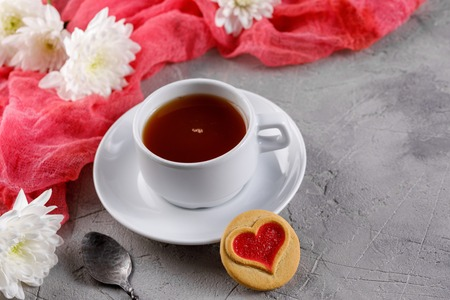 Cup of tea and cookies with hearts on a gray background. Beautiful still life with a cup of tea, the mood of Valentine's Day. Close-up. Banco de Imagens