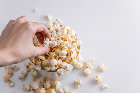 A hand is taking a popcorn from a paper bucket on a white background. Top view. Close-up.