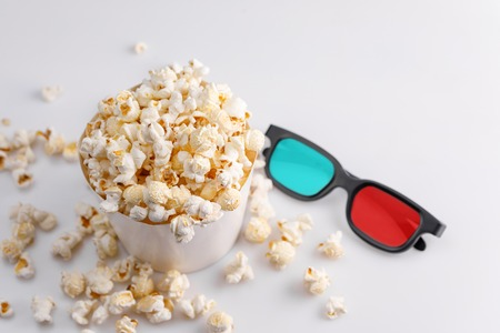 A bucket full of popcorn and glasses for watching 3 d movies. White background. Top view.